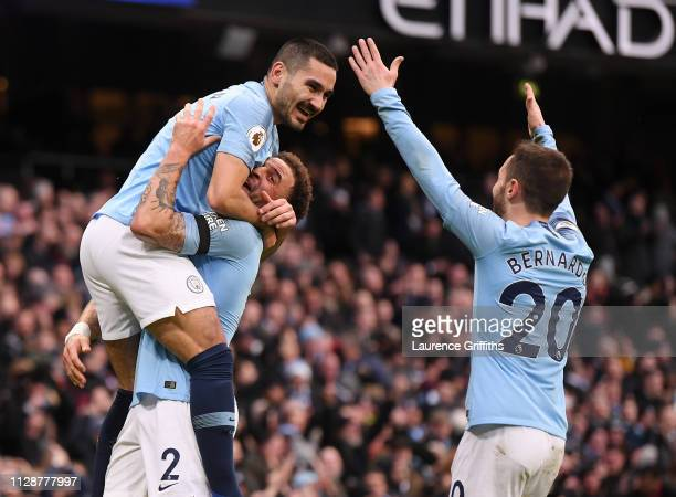 Ilkay Gundogan of Manchester City celebrates with teammates Kyle Walker and Bernardo Silva after scoring his team's fourth goal during the Premier...