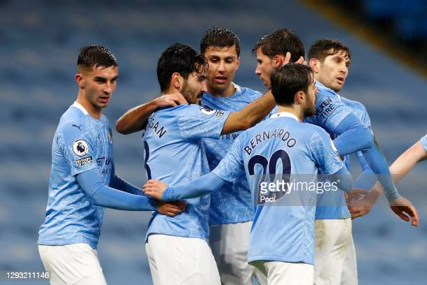 Ilkay Gundogan of Manchester City celebrates with teammates Ruben Dias and Rodri after scoring their sides first goal during the Premier League match...
