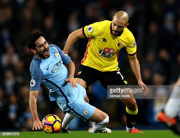 Ilkay Gundogan of Manchester City is challenged by Nordin Amrabat of Watford during the Premier League match between Manchester City and Watford at...