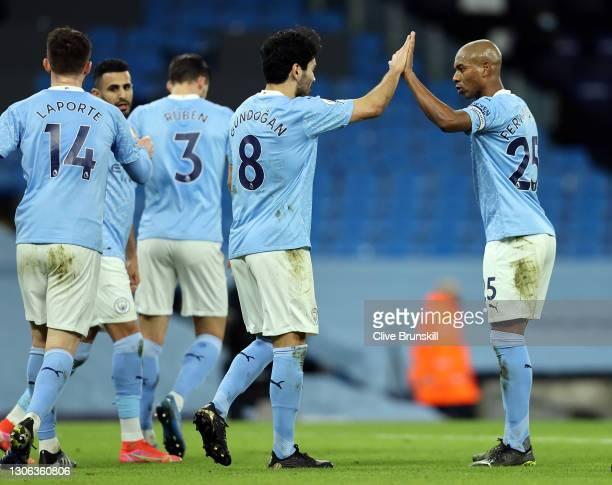 Ilkay Gundogan of Manchester City is congratulated by team mate Fernandinho after scoring their side's third goal during the Premier League match...