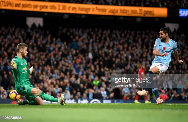 Ilkay Gundogan of Manchester City scores his team's third goal past David De Gea of Manchester United during the Premier League match between...