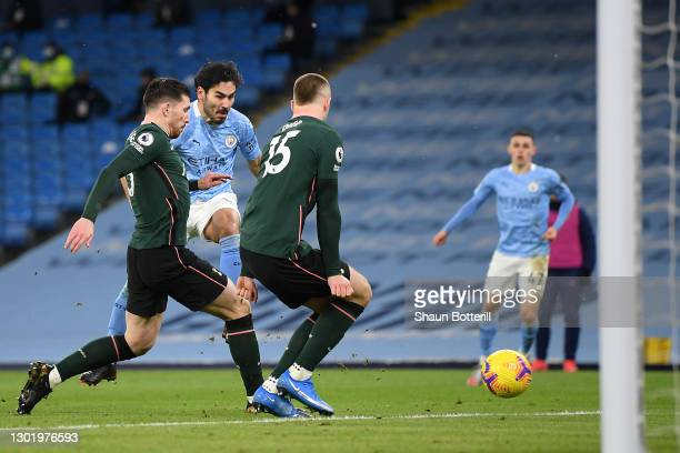 Ilkay Gundogan of Manchester City scores their side's second goal whilst under pressure from Pierre-Emile Hojbjerg and Eric Dier of Tottenham Hotspur...