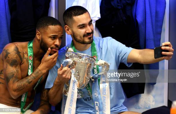 Ilkay Gundogan of Manchester City takes a selfie with Raheem Sterling of Manchester City and the trophy after winning the Carabao Cup Final between...
