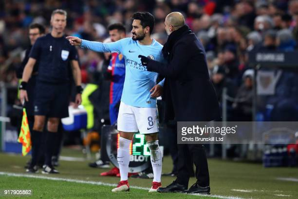 Ilkay Gundogan of Manchester City talks with Pep Guardiola Manager of Manchester City on the sideline during the UEFA Champions League Round of 16...