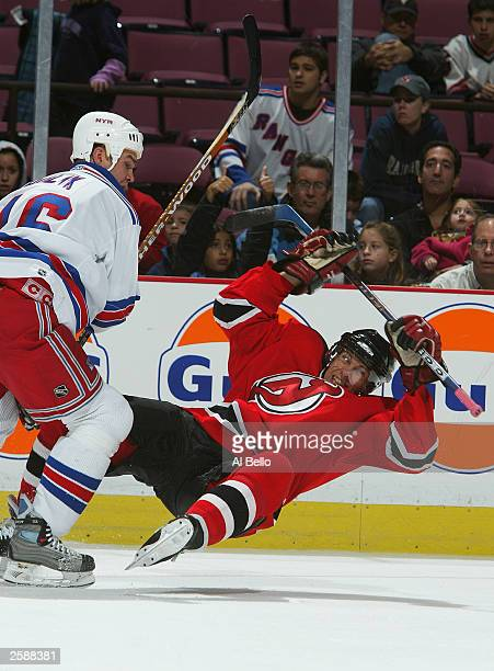 Ilkka Pikkarainen of the New Jersey Devils is checked by Bobby Holik of the New York Rangers on October 3 2003 at Continental Airlines Arena in East...