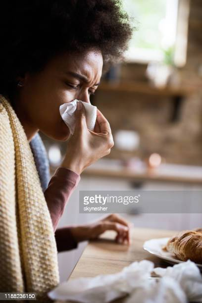 ill african american woman blowing her nose in dining room. - cold virus stock pictures, royalty-free photos & images