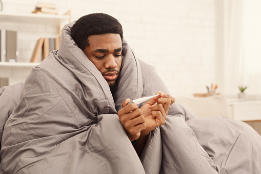 Ill man covered with blanket holding thermometer 1124421164