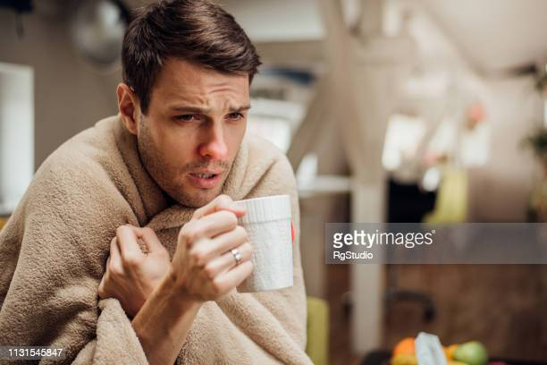 ill man drinking tea - shaking stock pictures, royalty-free photos & images