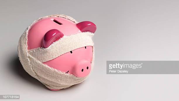 ill piggy bank with bandages - dívida imagens e fotografias de stock