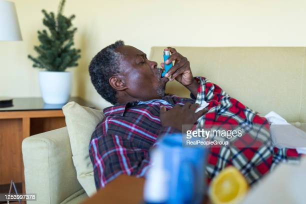 ill senior afro-american is using asthma inhaler - condition stock pictures, royalty-free photos & images
