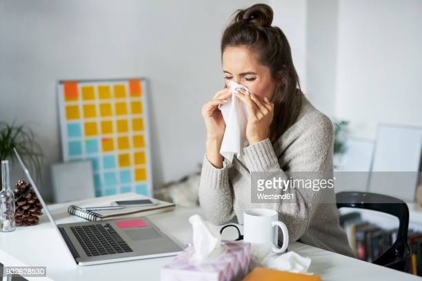 ill woman at home at desk blowing her nose - handkerchief - fotografias e filmes do acervo