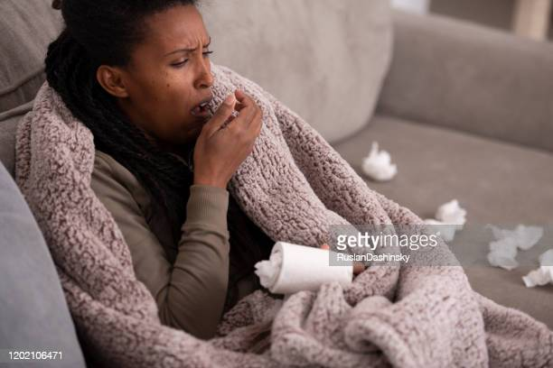 ill woman coughing covering mouth with the hand, sitting on couch. - nasal mucus stock pictures, royalty-free photos & images