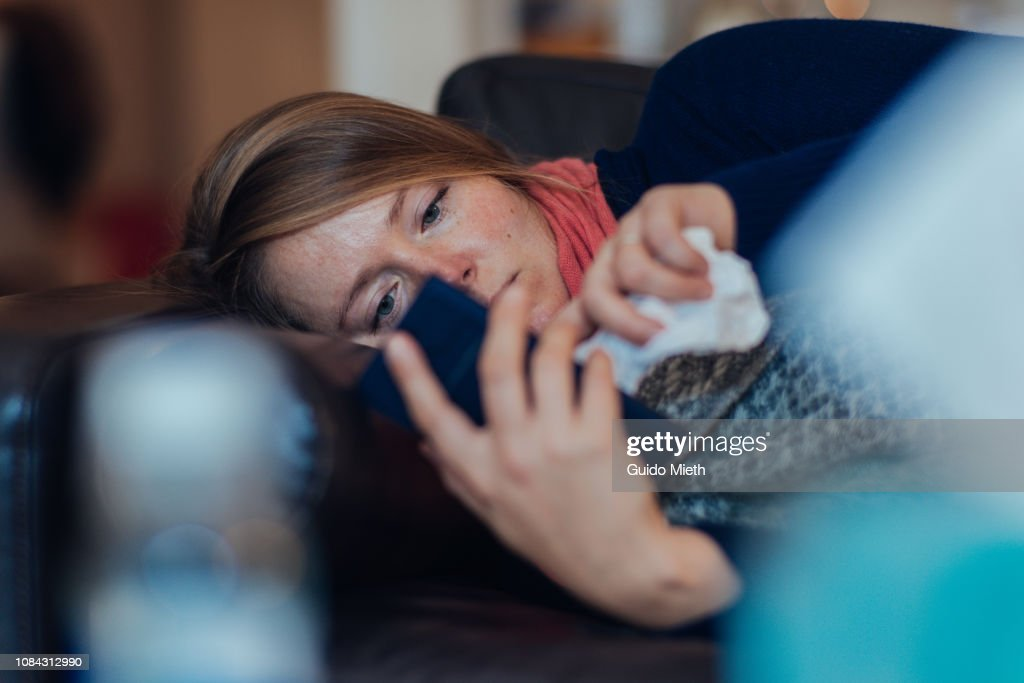 Ill woman using mobile phone. : Stock Photo