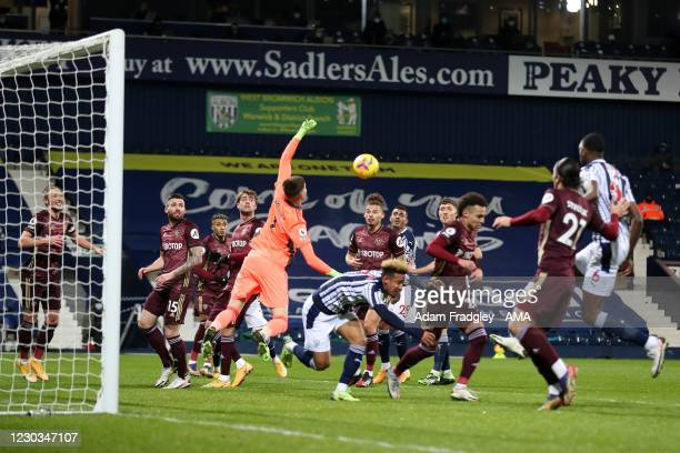 Illan Meslier of Leeds United punches the ball clear of danger as Semi Ajayi of West Bromwich Albion leaps to meet the free kick during the Premier...