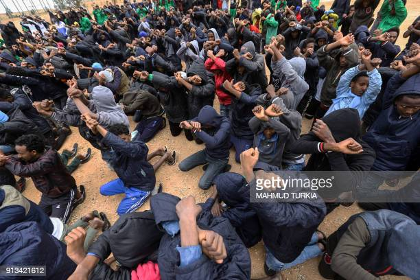 Illegal African migrants raise their hands crossed in a gesture protesting against their detention and demanding deportation to Europe at AlHamra...