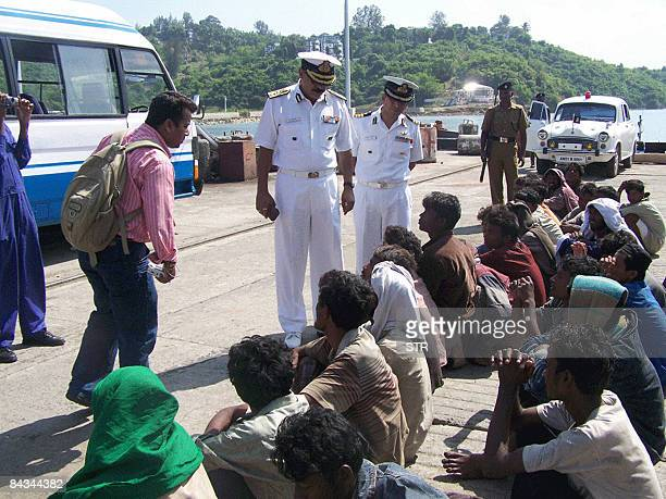 Illegal Bangladeshi migrants sit ashore after their rescue at sea by the Indian coastguard in Port Blair on January 8 2009 The Indian Coast Guard...