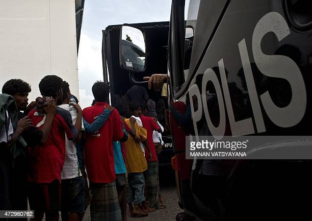 Illegal Bangladeshi migrants stand in a queue to board a police van at the police headquarters in Langkawi on May 11 2015 after landing on Malaysian...
