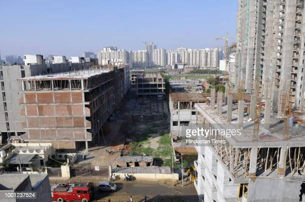 Construction workers sitting on roof of an under construction building near the two collapsed structures at Shahberi village on July 18 2018 in...