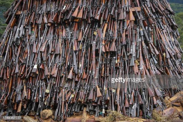 Illegal firearms are piled to burn at the Regional Police Traffic Training Centre in Ngong, Kenya, on June 9, 2021. - 5144 illegal firearms were...