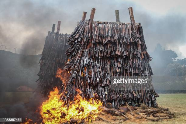 Illegal firearms are set on fire at the Regional Police Traffic Training Centre in Ngong, Kenya, on June 9, 2021. - 5144 illegal firearms were...
