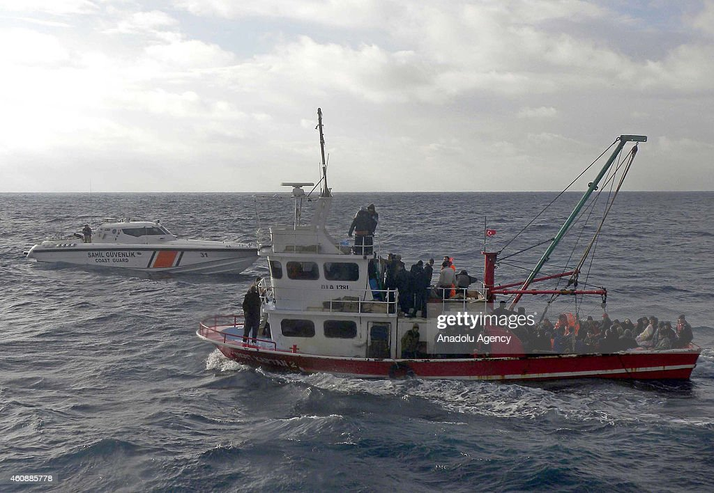Illegal immigrants are escorted by the officers of Turkey's Coast Guard Mediterranean Region Command as they arrive in Mersin, Turkey on December 29, 2014. Some Iraqi, Palestinian and Syrian 131 illegal migrants were captured while trying to illegally reach Europe on fishing boats.