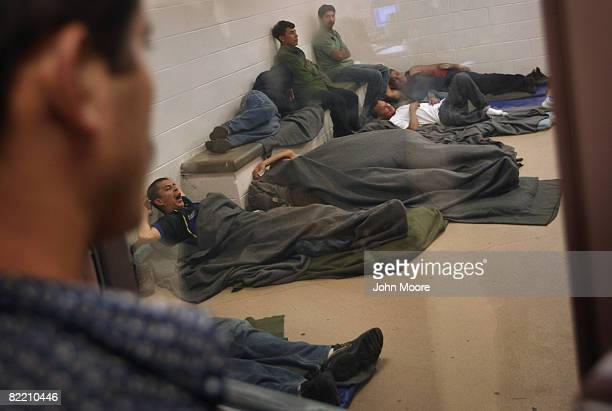 Illegal immigrants rest in a holding cell at a US Border Patrol station after they were caught crossing from Mexico into the United States August 7...