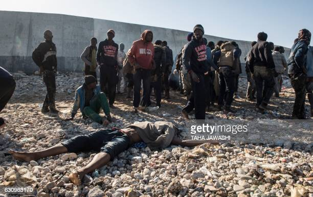 TOPSHOT Illegal immigrants stand next to a body after their boat washed ashore in the Andalus district of the capital Tripoli on January 4 2017 After...