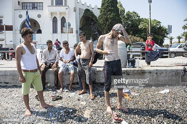 Illegal immigrants take a shower after they arrived in Greece's Kos island on September 4 2015 Migrants who have illegally travelled from Mugla's...