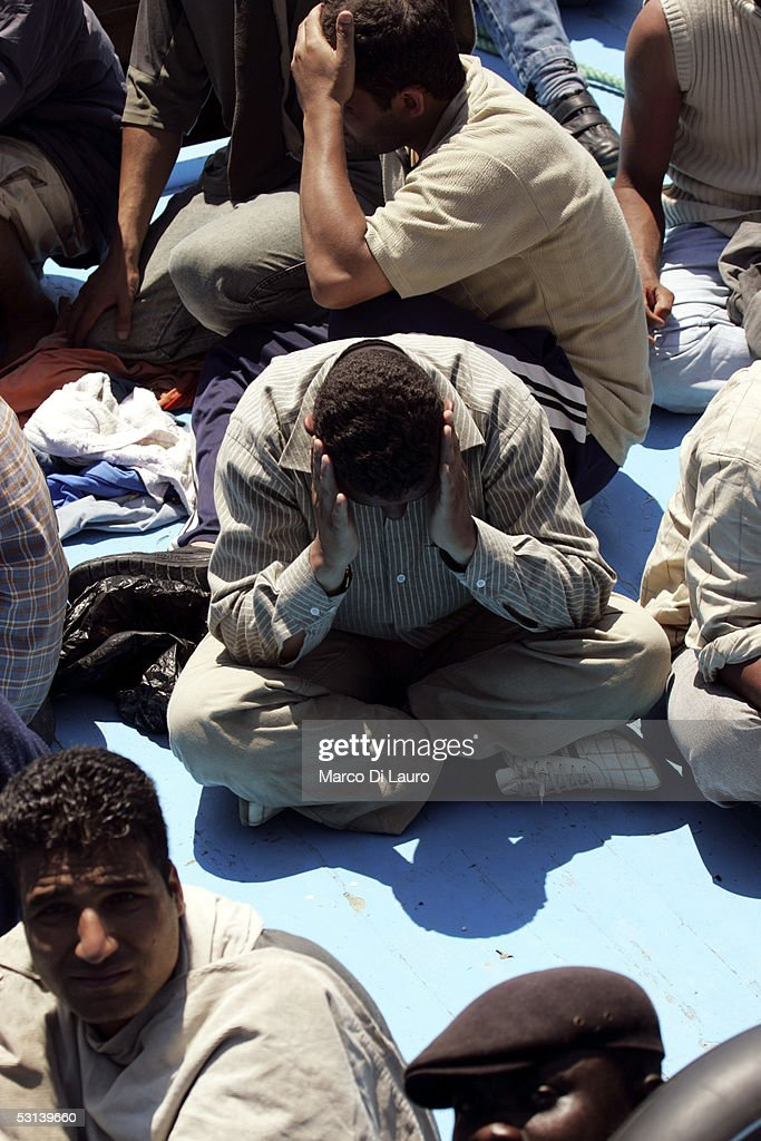 Illegal immigrants wait to be taken on board a boat of Italian Custom Police 'Guardia di Finanza' on June 21, 2005 in Lampedusa, Italy. Tens of thousands of immigrants land on the Italian coast each year, most of them heading from north Africa on ramshackle boats.In the Mediterranean Sea between Malta and Tunisia, Lampedusa Island is one of the main gateways for illegal immigration from Africa into Europe. According to a report by Amnesty International, Illegal immigrants who land in Italy consistently allege they have been abused, holding centres are overcrowded and no legal assistance is offered. Italian authorities refused to give access to the centres to enable further investigations by Amnesty. The Amnesty International report says 15,647 people were held in the centres in 2004: a 9 per-cent increase on the previous year.