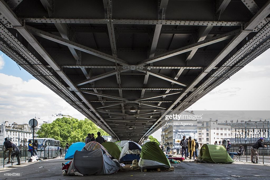 Illegal migrants are seen at an unauthorized migrant camp under the tracks of the Paris Metro Line 2 on Boulevard de la Chapelle in Paris, France on June 01, 2015. Authorities ordered the closure of illegal migrants camp in northern suburb fearing disease & epidemic. Hundreds of African migrants living in a shantytown in northern Paris, women and children among them, have been told to leave their tent camp after authorities said they posed high risks of epidemic sicknesses spreading in the French capital.