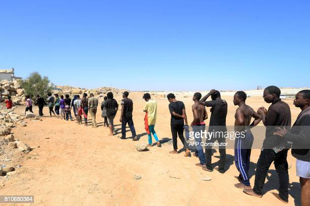Illegal migrants from Africa attempting to reach Europe walk towards a detention center off the coastal town of Guarabouli 60 kilometres east of the...
