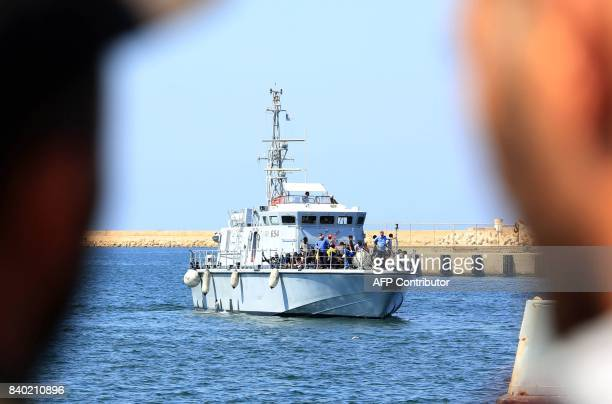 Illegal migrants from Africa sit on a Libyan coastguard boat as they arrive at a naval base in Tripoli after being rescued in the Mediterranean Sea...