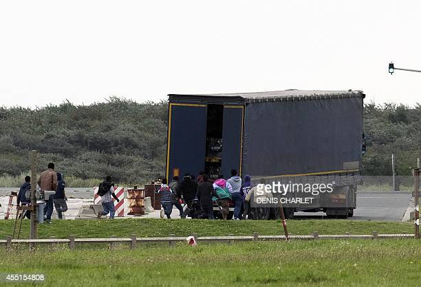 Illegal migrants run toward a truck about to board a ferry to Great Britain on September 10 2014 in the French port of Calais Illegal camps of...