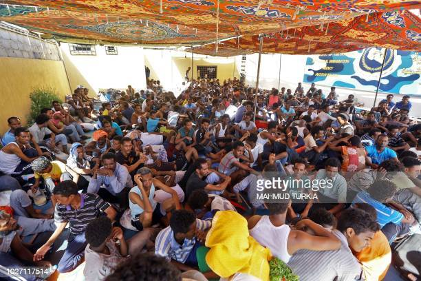 TOPSHOT Illegal migrants sit inside the Ganzour shelter after being transferred from in the airport road due to fighting in the Libyan capital...