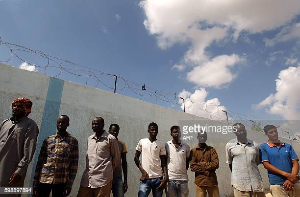 TOPSHOT Illegal migrants wait to receive aid distribution provided by the International Organization for Migration in cooperation with the Libyan Red...