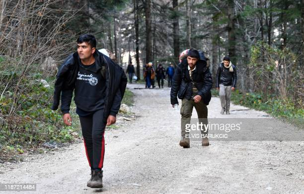 """Illegal migrants walk on a forest trail towards the Croatian border, after leaving the improvised camp """"Vucjak"""", on the outskirts of the northern..."""