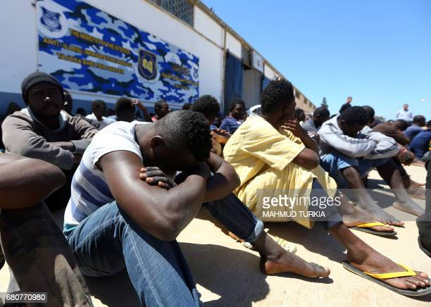 Illegal migrants who were found by Libyan security forces while waiting in a depot in Tripoli's eastern suburb of Tajoura prior to being smuggled to...