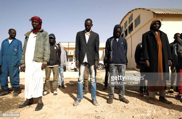TOPSHOT Illegal subSaharan migrants stand at the Qanfouda detention centre in the southern outskitrs of Benghazi before being repatriated on December...