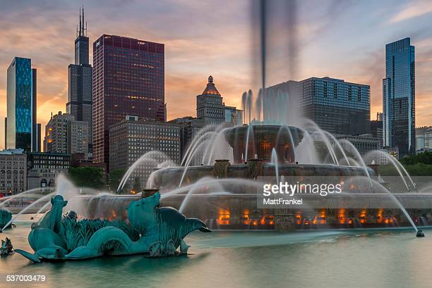 usa, illinois, chicago, buckingham fountain and skyscrapers against evening sky - chicago illinois fotografías e imágenes de stock