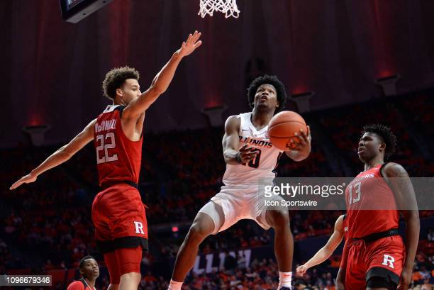 Illinois Fighting Illini guard AndresFeliz throws an underhanded shot at the basket as Rutgers Scarlet Knights guard Caleb McConnell and Rutgers...