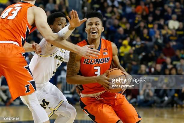 Illinois Fighting Illini guard Te'Jon Lucas drives to the basket against Michigan Wolverines guard Zavier Simpson during a regular season Big 10...