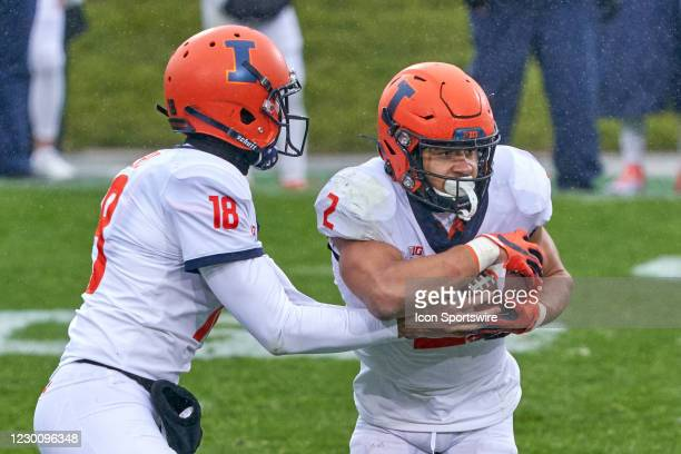 Illinois Fighting Illini quarterback Matt Robinson hands the football to Illinois Fighting Illini running back Chase Brown in action during a game...