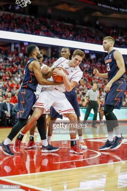 Illinois guard Mark Alstork and Wisconsin forward Nate Reuvers battle for control of the ball during a college basketball game between the University...