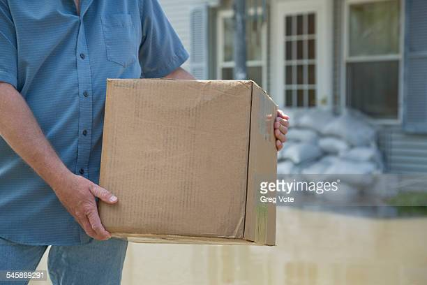 usa, illinois, man carrying package during flood - emergency management stock pictures, royalty-free photos & images