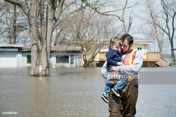 usa, illinois, man with son wading in floodwaters - 危機管理 ストックフォトと画像