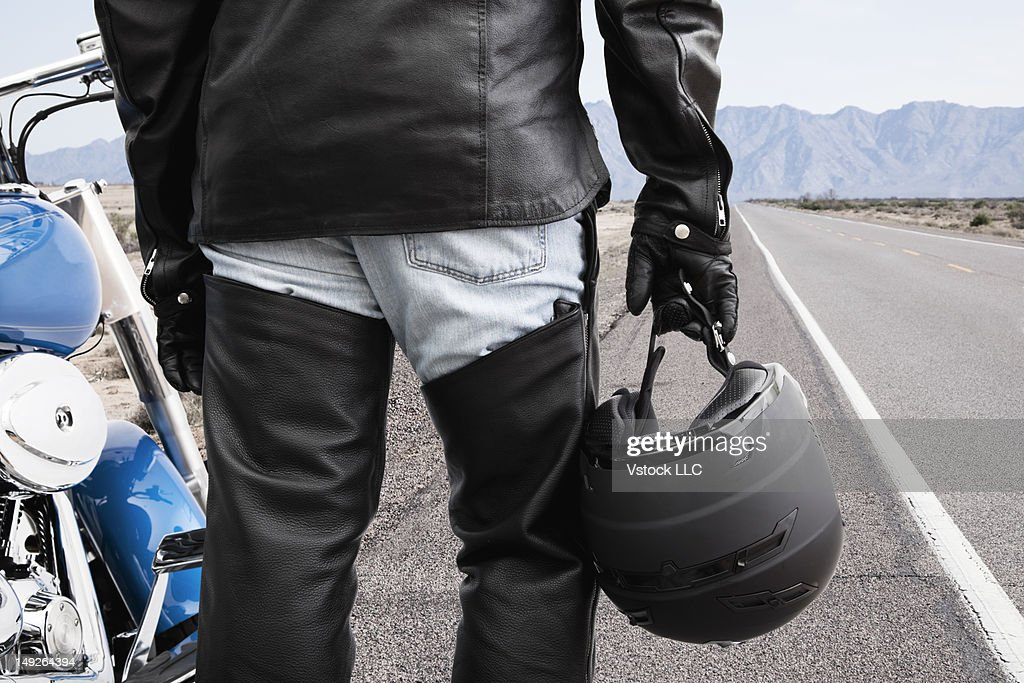 USA, Illinois, Metamora, Biker on road holding crash helmet : Stock Photo
