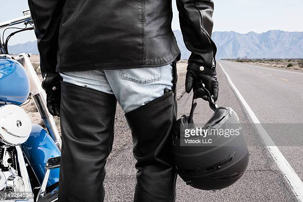 USA, Illinois, Metamora, Biker on road holding crash helmet