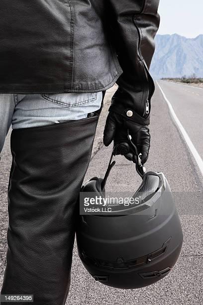 USA, Illinois, Metamora, Biker on road holding crash helmet
