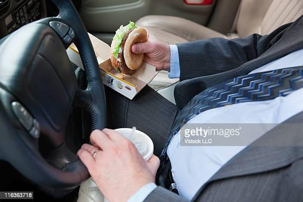 USA, Illinois, Metamora, Close-up of man eating hamburger while driving car