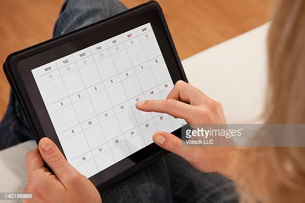 USA, Illinois, Metamora, Close-up of woman using calendar on digital tablet